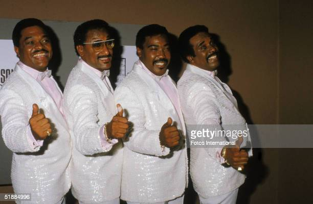 The Four Tops dressed in matching sequinned white tuxedos pink shirts and white bow ties give the thumbs up backstage at an unidentified event 1980s...