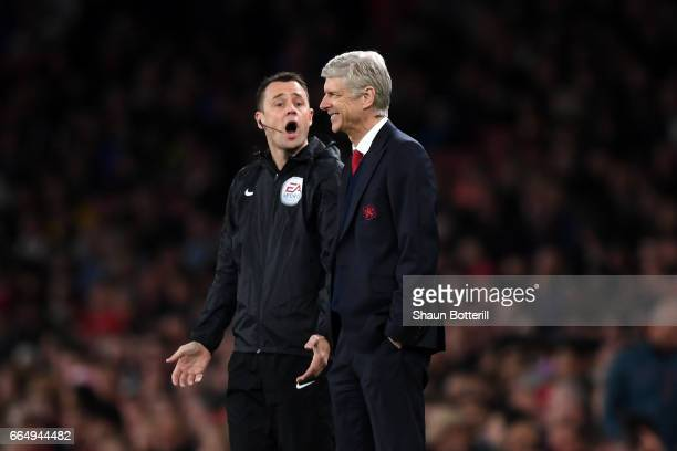 The fourth offical and Arsene Wenger Manager of Arsenal exchange words during the Premier League match between Arsenal and West Ham United at the...