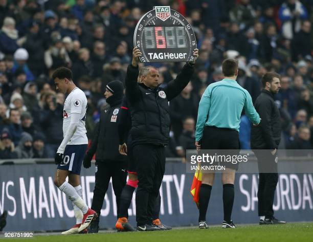 The fourth official holds the board for Tottenham Hotspur's English midfielder Dele Alli substitution during the English Premier League football...