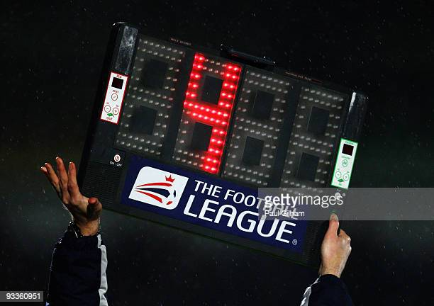 The fourth official holds up a board indicating four minutes of extra time to be played at the end of the first half during the CocaCola League One...