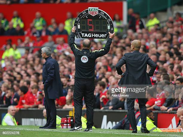 The fourth official holds up the extra time board during the Premier League match between Manchester United and Manchester City at Old Trafford on...