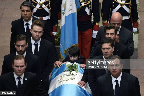 The fragdraped coffin of Guatemala City Mayor and former Guatemalan President Alvaro Arzu is escorted by his sons and grandchildren during a ceremony...