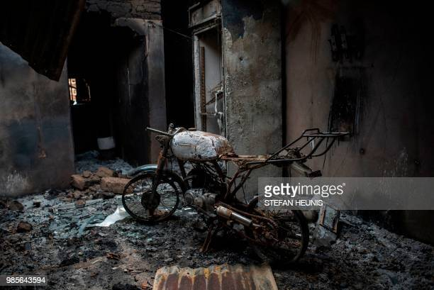 TOPSHOT The frame of a burnt out motorcycle is seen in a house burned down by Fulani herdsman in the Ganaropp village in the Barikin Ladi area near...