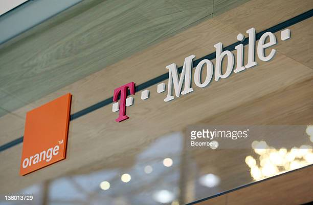 The France Telecome SA's Orange brand logo left and the Deutsche Telekom AG's TMobile brand logo are displayed outside a store operated by Everything...