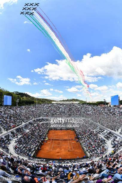 The Frecce Tricolori air squadron flies over the Foro Italico as Serbia's Novak Djokovic plays against Canada's Denis Shapovalov during their ATP...