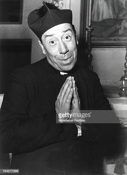 The French actor Fernandel in cassocks in the role of Don Camillo smiling with hands joined as praying Italy 1952