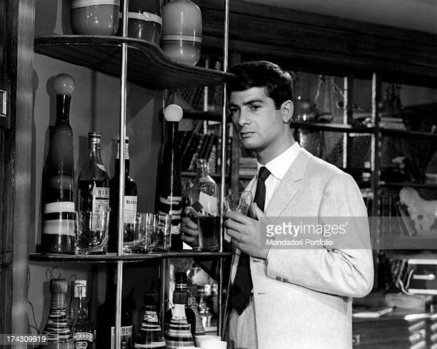 The French actor JeanClaude Brialy playing the leading role of Jacky in Deray's The gigolo is near a shelf of liquors with a glass in his hand France...