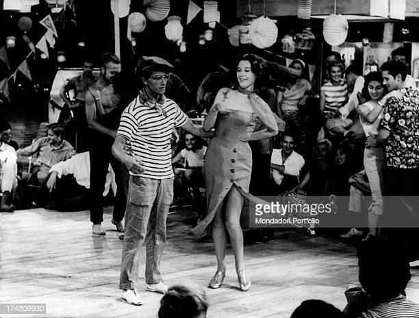 The French actors Darry Cowl and Beatrice Altariba are dancing together on a dancefloor, surrounded by young people dancing and having fun at a...