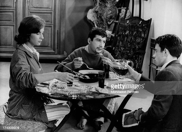 The French actors Juliette Mayniel JeanClaude Brialy and Gerard Blain are seated at a round table having lunch in a scene from Claude Chabrol's The...