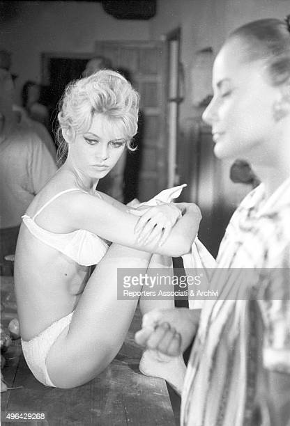 The French actress Brigitte Bardot sitting on a table in underwear on the set of the film The Night Heaven Fell Spain 1958