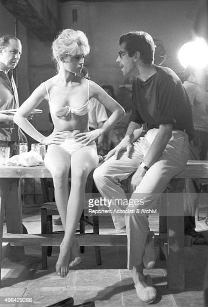 The French actress Brigitte Bardot sitting on a table talking with the French director Roger Vadim on the movie set of The Night Heaven Fell Spain...