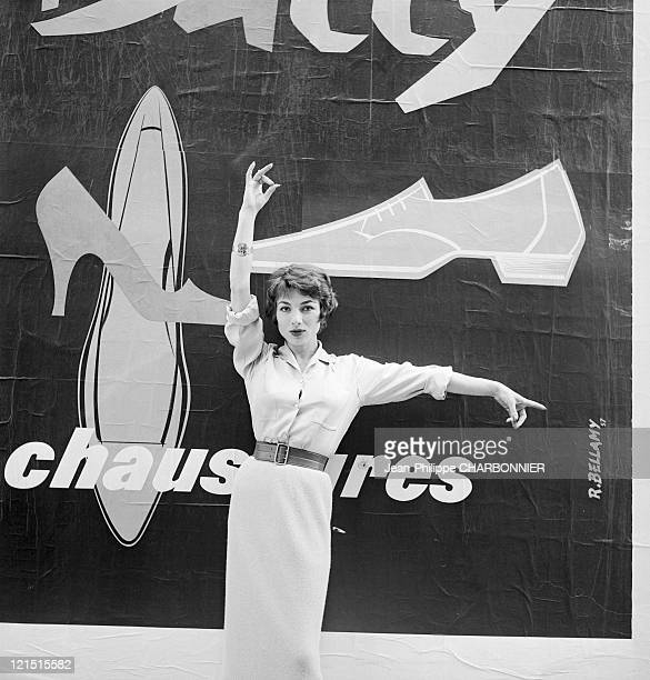 The French Actress Judith Magre Posing In Front Of A Poster For Bally Shoes Around 1960