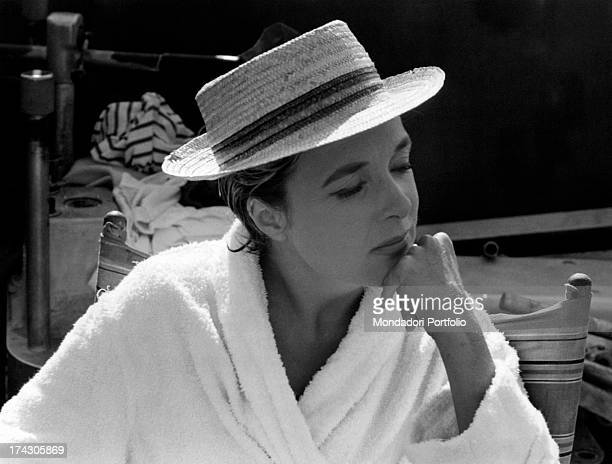 The French actress Micheline Presle born Micheline Chassagne wearing a bathrobe and a hat is seated resting her chin on a hand during the making of...