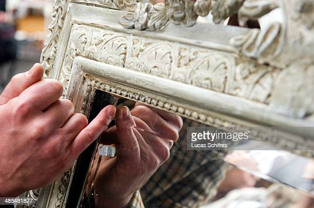 The French Collection TV presenter Mark Franks points to details of a centuryold bevelled mirror in SaintOuen flea market on February 8 outside Paris...
