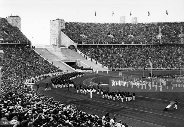 The French delegation marches through the new 100 000 seat Berlin stadium as the crowd gives the nazi salute during the opening ceremony of the...