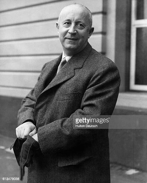 The French fashion designer Christian Dior puts his gloves on outside London's Victoria Station He is in Britain to attend a fashion show at Blenheim...