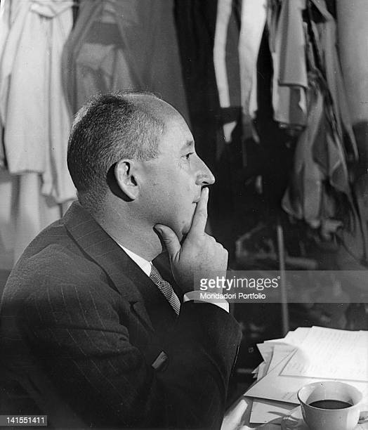 The French fashion designer Christian Dior sitting at the desk of his atelier. Paris, 1940s