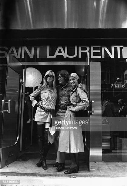 The French fashion designer Yves St Laurent poses with two of his friends Betty Catrox and Louise de la Falaise, wearing his own designs, outside his...