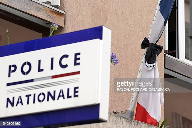 The French flag above the Ajaccio police station is pictured at halfmast on June 15 2016 as police officers observe a minute of silence in the memory...