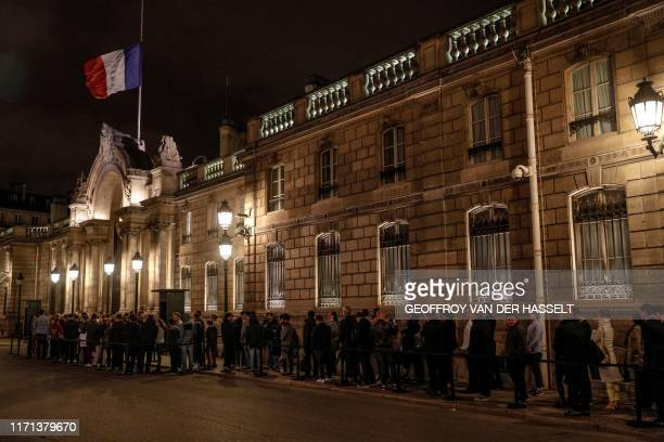 TOPSHOT The French flag flies at half mast over the front entrance of the Elysee presidential palace in Paris on September 26 2019 as people queue to...