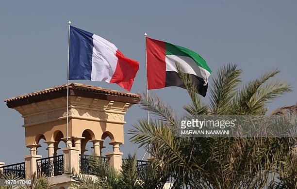 The French flag flutters near the UAE flag in respect to the victims of the attacks in Paris during the DP World Tour Championship in Dubai on...