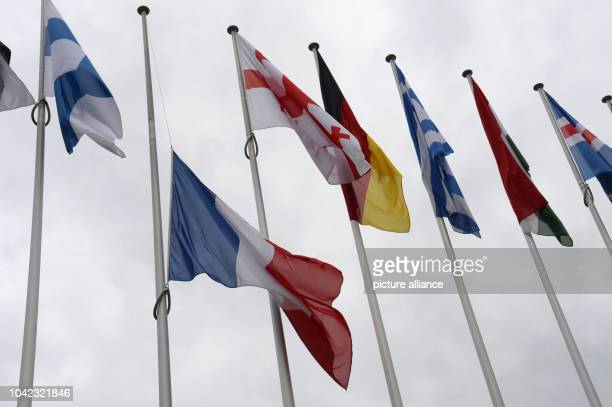 The French flag 'Tricolore' sways on half-mast after the terrorist attack on the French satire magazine 'Charlie Hebdo' in front of the Council of...