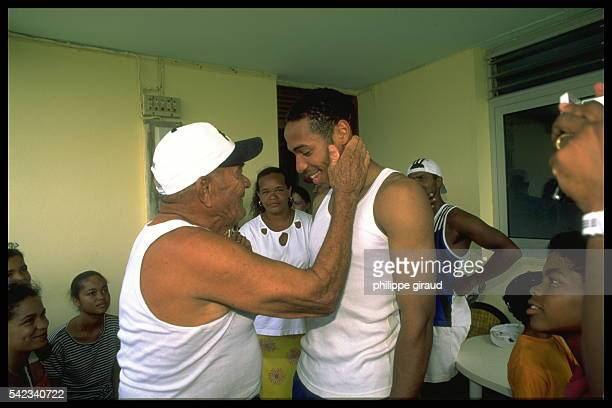 The French footballer greets his grandfather at the family home on La Desirade Island