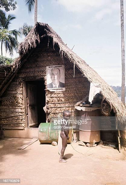 The French Guiana En Guyane française en février 1975 un enfant nu tenant un bâton à la main devant une hutte sur laquelle est affiché le portrait du...