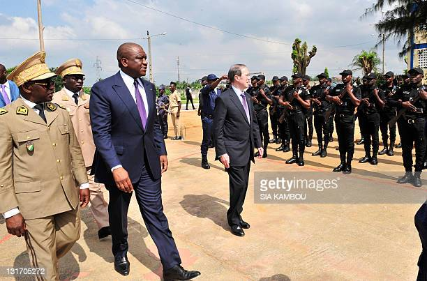 The French Minister of the Interior Claude Gueant walks past Ivorian police officers at a police training school in Abidjan alongside his Ivorian...