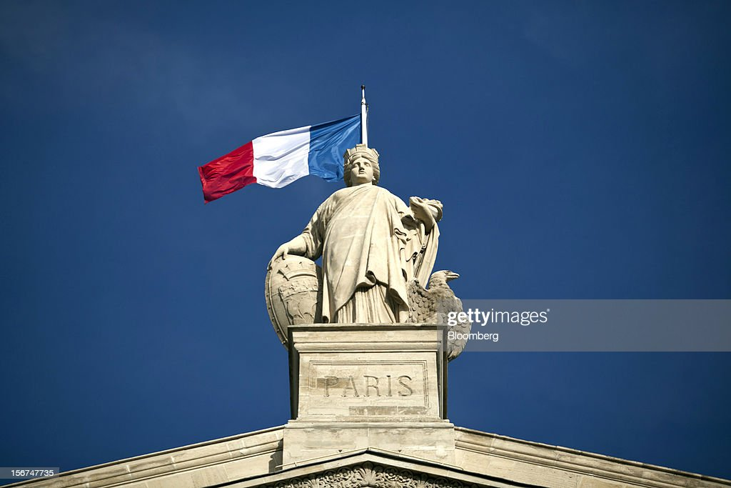 The French national flag is seen flying from the roof of the Paris Nord train station in Paris, France, on Tuesday, Nov. 20, 2012. France's government bonds fell, with 10-year yields rising the most in a month, after Moody's Investors Service lowered the nation's top credit rating, citing a worsening economic growth outlook. Photographer: Balint Porneczi/Bloomberg via Getty Images