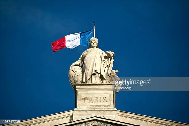 The French national flag is seen flying from the roof of the Paris Nord train station in Paris, France, on Tuesday, Nov. 20, 2012. France's...