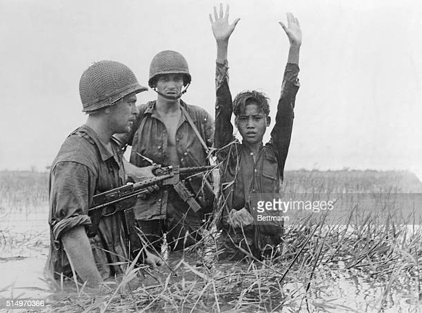 The French National Forces paratroopers stand here in swamp water, waist high, as they flush out a guerilla of the Communist Viet Minh forces.
