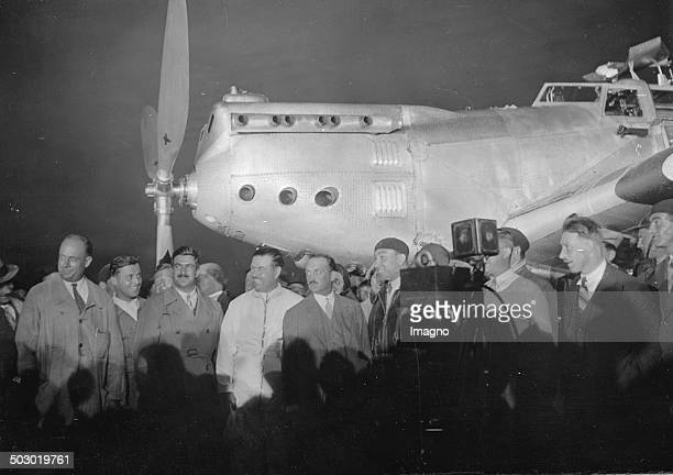 The French pilots René Mesmin and Joseph Le Brix and Marcel Doret before her record-breaking flight from Paris to Tokyo. In the background her plane...
