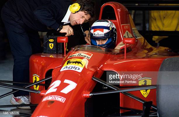The French racing driver Alain Prost is sitting in the passenger compartment of his Ferrari which is stationery at the pit and he is intent on...