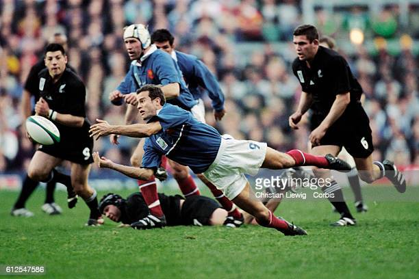 The French scrum half Fabien Galthie makes a diving pass during a semifinal of the 1999 Rugby Union World Cup against New Zealand