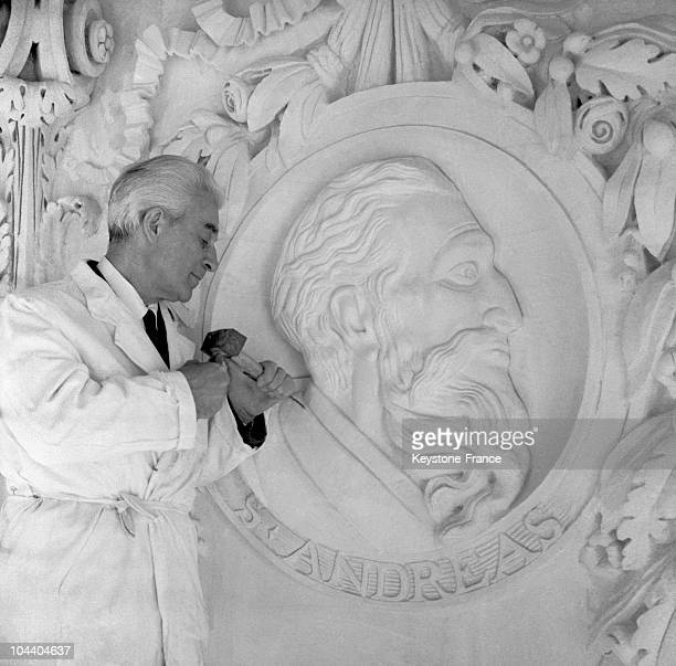 The French sculptor Paul BELMONDO a professor at Paris fine arts school finishing to sculpt a medallion representing one of the twelve apostles