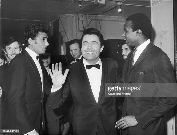 The French singer Alain BARRIERE with his fans the runners Michel JAZY and Roger BAMBUCK in a dressing room at the Olympia