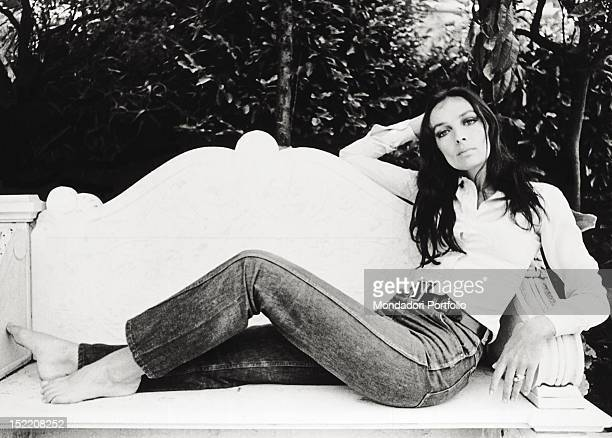 The French singer and actress Marie Laforet posing laid on a bench San Remo September 1968