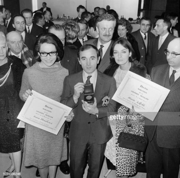 The French singer of Armenian origin Charles Aznavour poses with the singers Nana Mouskouri and Marie Laforêt on February 20 1964 in the house of the...
