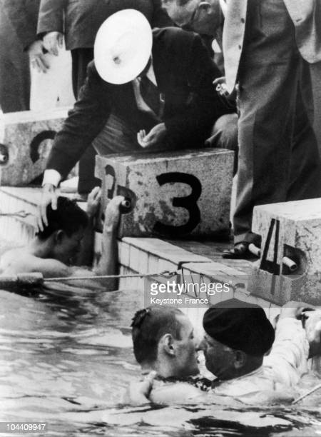 The French swimmer Jean BOITEUX being congratulated by his father who ecstatic dived into the pool fully dressed after his son's victory in the 400m...