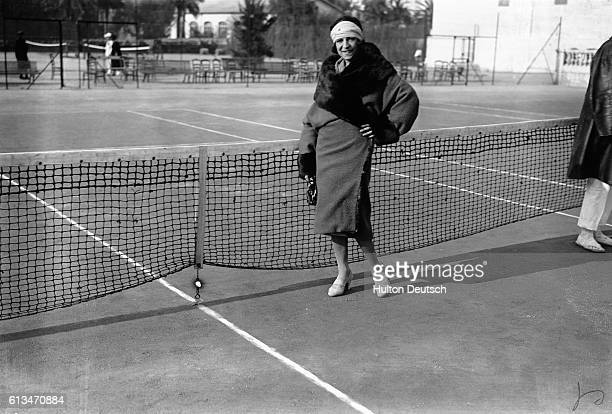 The French tennis player Suzanne Lenglen poses beside the net at a fashionable resort on the French Riviera. | Location: Cote d' Azur, France.