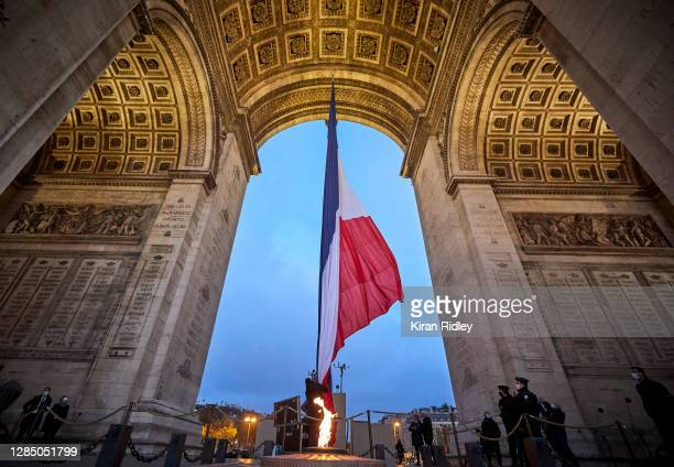 The French Tricolor Flag is raised above the Eternal Flame and the Tomb of the Unknown Soldier at the Arc de Triomphe as preparations begin for...