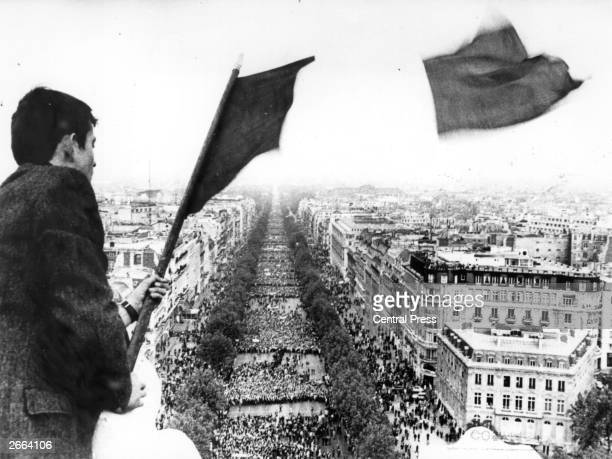 The French tricolour flies high over crowds marching to l'Arc de Triomphe during the Paris student's strike