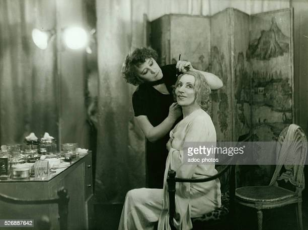 The French writer Colette applying make up on the French actress C��cile Sorel . Ca. 1930.