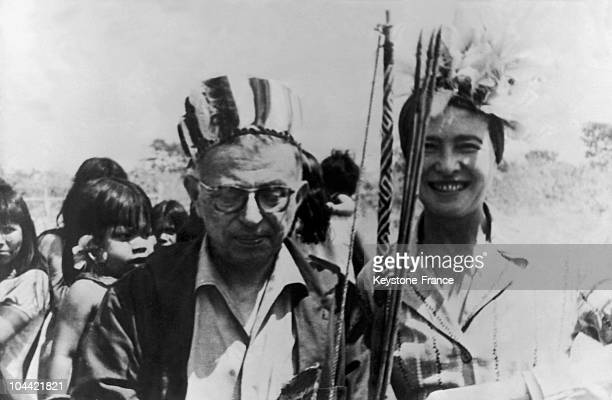 The French Writer JeanPaul Sartre And His Wife Simone De Beauvoir Wearing NativeAmerican Style Hats Holding Bows And Arrows Offered Them By The...