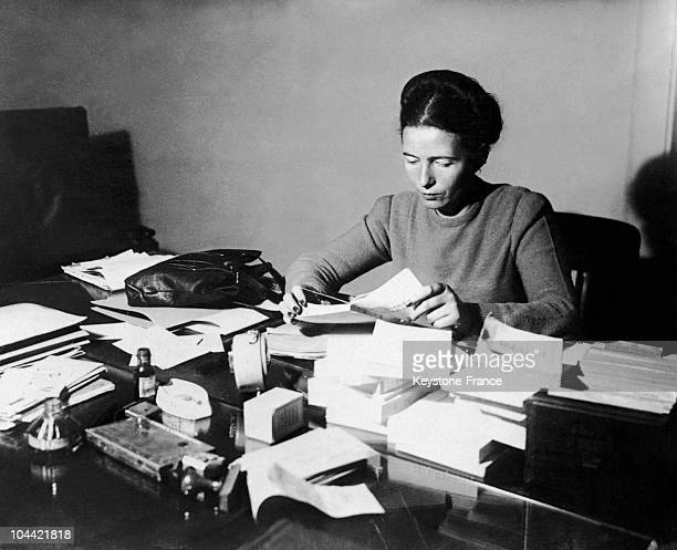 The French Writer Simone De Beauvoir Seated Reading At Her Desk In 1953