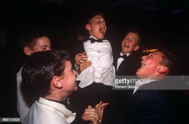 The friends of a young 13 yearold Jewish boy help celebrate his comingofage at his bar bar mitzvah party on 12th February 2001 in London England