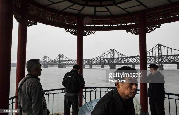 The Friendship Bridge is seen in the background as Chinese men take part in morning exercises on the Yalu river in the border city of Dandong...