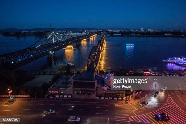 The Friendship Bridge left and Broken Bridge are seen as a train crosses on the Yalu river from the border city of Dandong Liaoning province northern...