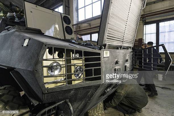 The front body panels of a DozorB armored car stand open for worker access during assembly on the production line in the military workshop operated...